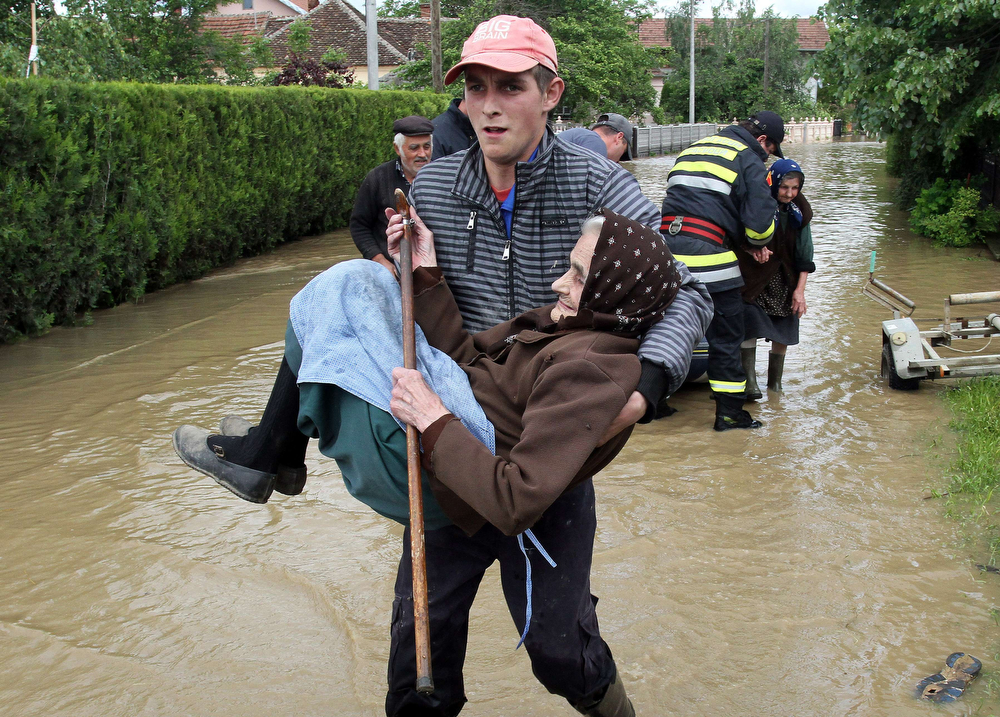 Description of . A Serbian rescuer carries an elderly woman out of her flooded house in the village of Obrez, near the central Serbian town of Varvarin, south of Belgrade, on May 17, 2014. Deadly floods across Bosnia and Serbia have claimed at least 14 lives and led to the evacuation of 15,000 people after the Balkans suffered its heaviest rainfall in a century, officials said on Saturday.  (SASA DJORDJEVIC/AFP/Getty Images)