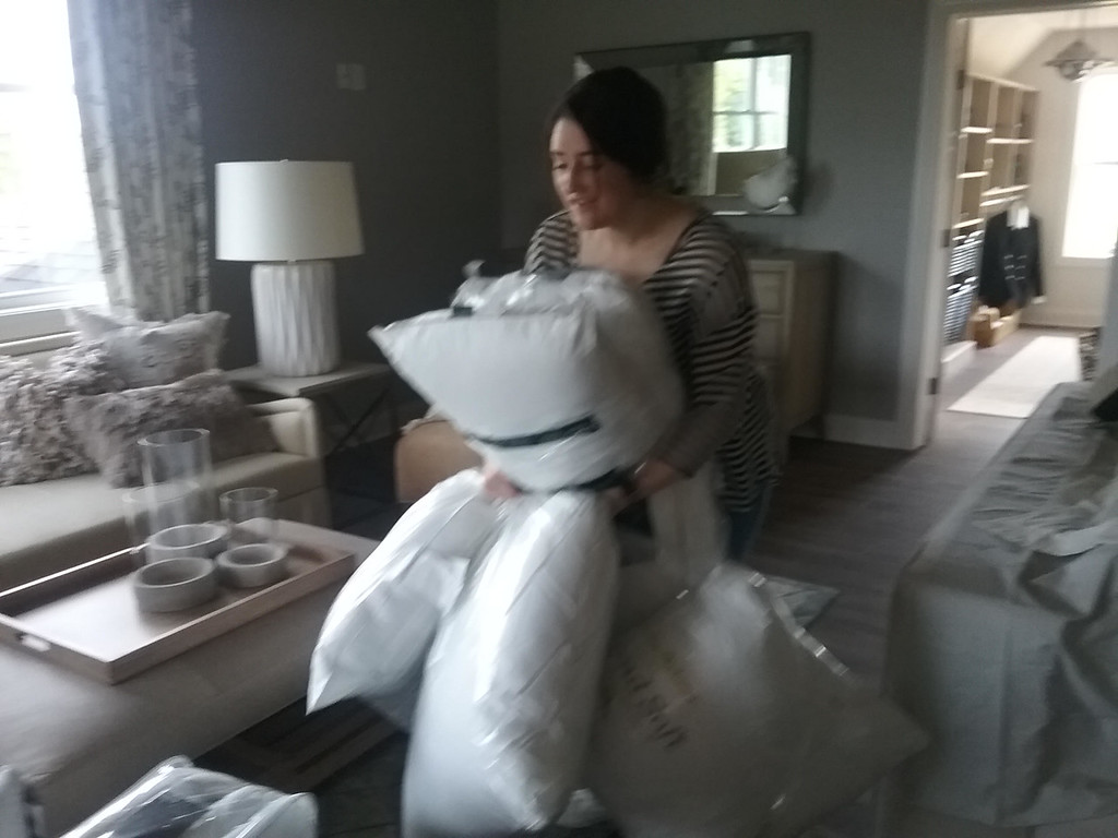 . Design intern Kate Spansel of Mentor carries a bundle of pillows for use in the master suite of the 2018 Dream House. (Jean Bonchak)