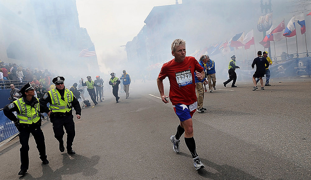 . A Boston Marathon competitor and Boston police run from the area of an explosion near the finish line in Boston, Monday, April 15, 2013. (AP Photo/MetroWest Daily News, Ken McGagh)