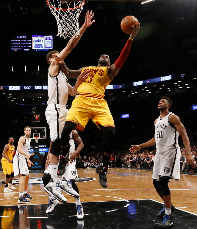 . Brooklyn Nets center Brook Lopez (11) defends Cleveland Cavaliers forward LeBron James (23) who goes up for a layup in the fourth quarter of an NBA basketball game, Thursday, March 24, 2016, in New York. James had 20 points but the Nets beat the Cavaliers 104-95. Brooklyn Nets forward Thaddeus Young (30) watches from the floor. (AP Photo/Kathy Willens)