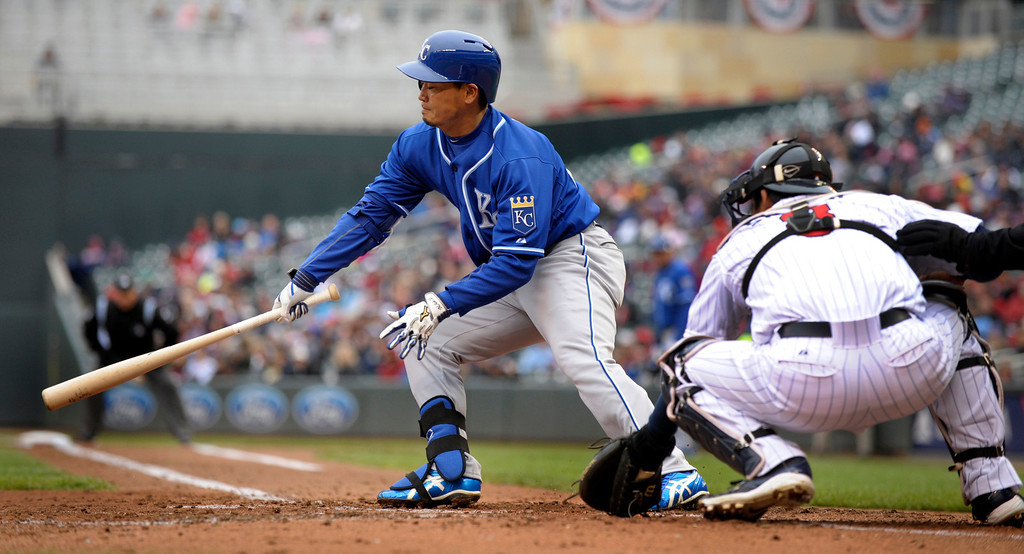 . Kansas City Royals� Nori Aoki, of Japan, hits a grounder during the third inning. Twins catcher Kurt Suzuki, right, awaits the pitch. Lorenzo Cain was out, and Aoki was safe at first. (AP Photo/Tom Olmscheid)