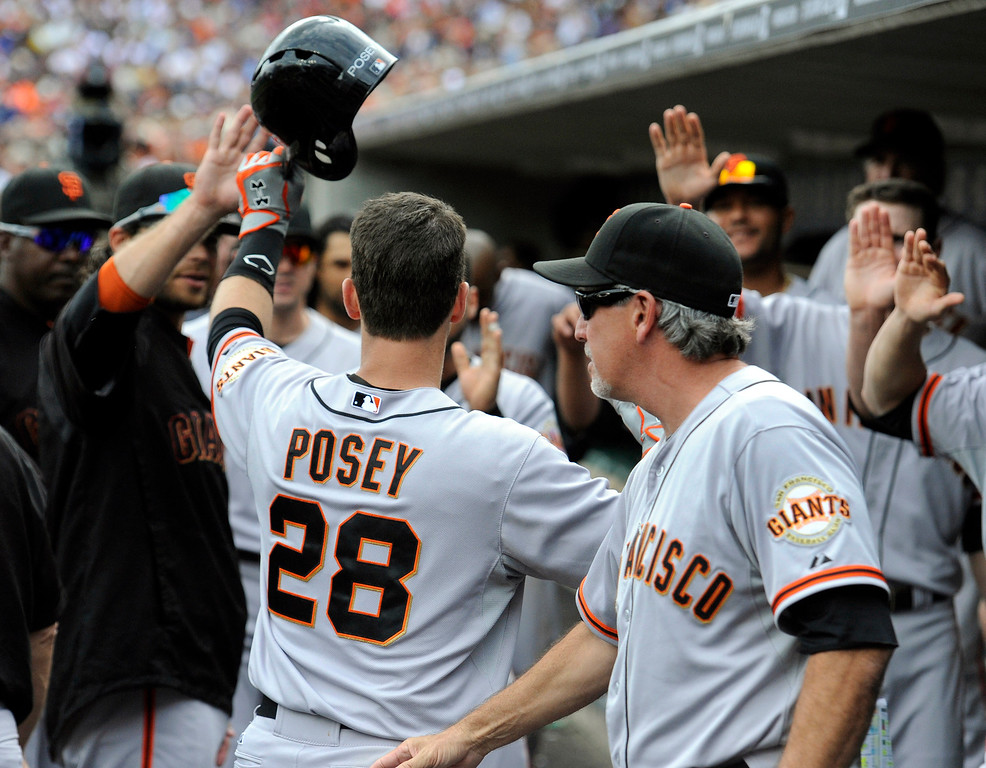 . San Francisco Giants\' Buster Posey, left, high-fives teammates after hitting a home run against the Detroit Tigers in the fifth inning of a baseball game Saturday, Sept. 6, 2014, in Detroit.  The Giants won 5-4.  (AP Photo/Jose Juarez)