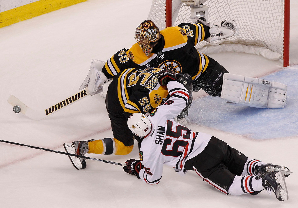 . Boston Bruins goalie Tuukka Rask makes a save as Chicago Blackhawks\' Andrew Shaw (65) takes down Bruins\' Johnny Boychuk during the third period in Game 6 of their NHL Stanley Cup Finals hockey series in Boston, Massachusetts, June 24, 2013. REUTERS/Adam Hunger