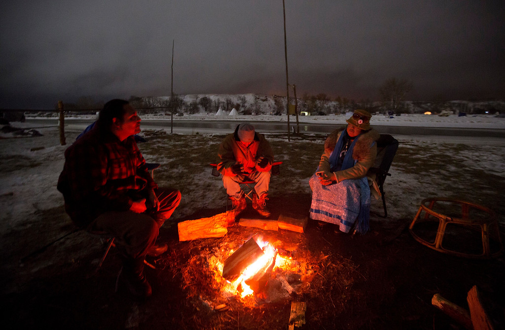 . In this Thursday, Dec. 1, 2016 photo, Joseph Hill, a Seneca Native American, sits with Popz Longwalker, A Cherokee Native American, and Dawn of the Day, a Dakota Native American around a fire along the Cannonball river at the Oceti Sakowin camp where people have gathered to protest the Dakota Access pipeline in Cannon Ball, N.D. So far, those fighting the Dakota Access pipeline have shrugged off the heavy snow, icy winds and frigid temperatures that have swirled around their encampment on the North Dakota grasslands. But if they defy next week\'s government deadline to abandon the camp, demonstrators know the real deep freeze lies ahead. (AP Photo/David Goldman)
