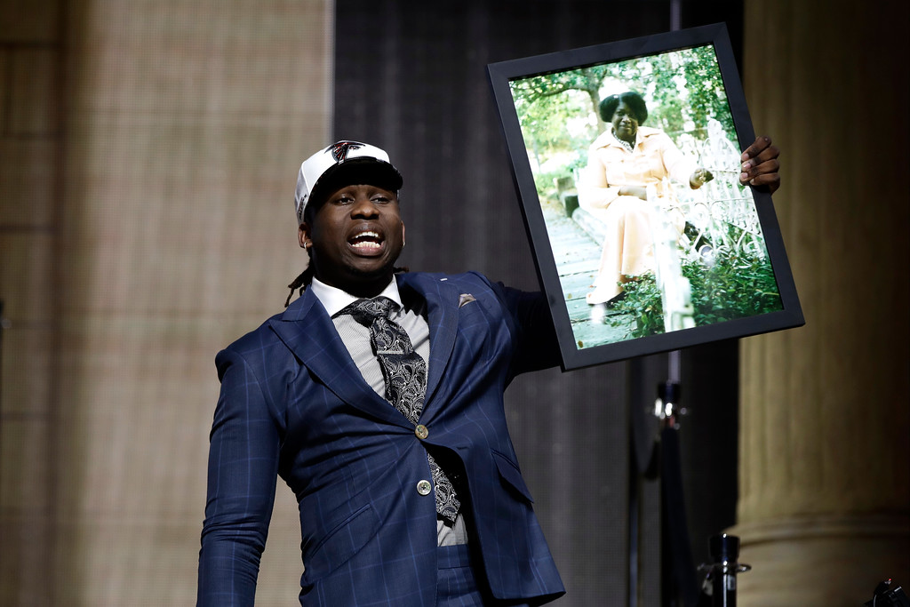 . UCLA\'s Takkarist McKinley carries a photograph of his grandmother onstage after being selected by the Atlanta Falcons during the first round of the 2017 NFL football draft, Thursday, April 27, 2017, in Philadelphia. (AP Photo/Matt Rourke)