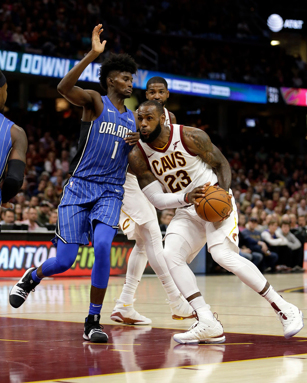 . Cleveland Cavaliers\' LeBron James (23) drives past Orlando Magic\'s Jonathan Isaac (1) in the first half of an NBA basketball game, Saturday, Oct. 21, 2017, in Cleveland. (AP Photo/Tony Dejak)