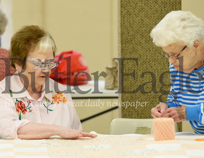 Harold Aughton/Butler Eagle: Dottie Slomer and Genny Retting work together to create a quilt at St. Marks Luthern Church.