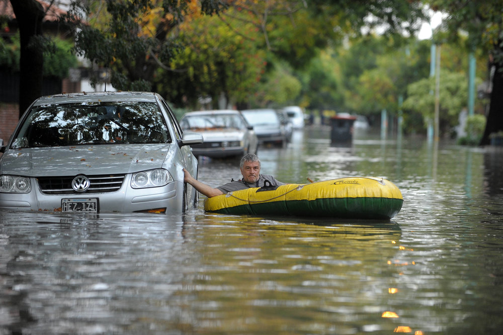 . A man maneuvers with his inflatable dinghy after heavy rains lashed Buenos Aires on April 2, 2013.  A violent storm with torrential rain and powerful wind left five people dead Tuesday in Buenos Aires as it knocked out power, downed trees and damaged homes, officials said. AFP PHOTO/TELAM/ Fernando Sturla
