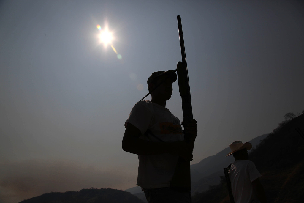 . In this May 20, 2013 photo, an armed man from a local self-defense group stands with his weapon at the entrance of the town of Buenavista, Mexico. Self-defense groups started to spring up in February to fight back the Knights Templar drug cartel which is extorting protection payments from cattlemen and lime growers, butchers and even marijuana growers. The federal government sees both the self-defense forces and the cartel as dangerous enemies. (AP Photo/Marco Ugarte)