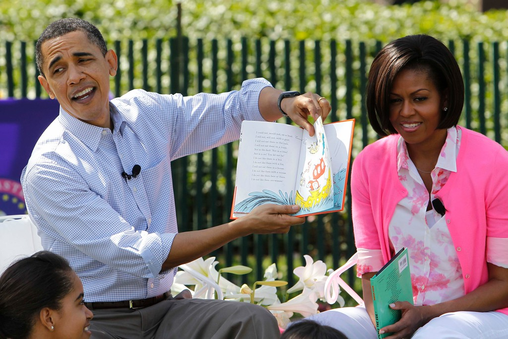 ". President Barack Obama, accompanied by first lady Michelle Obama and daughter Malia Obama, reads ""Green Eggs and Ham\"", as they hosted the annual White House Easter Egg Roll, Monday, April 5, 2010, on the South Lawn of the White House in Washington. (AP Photo/Charles Dharapak)"