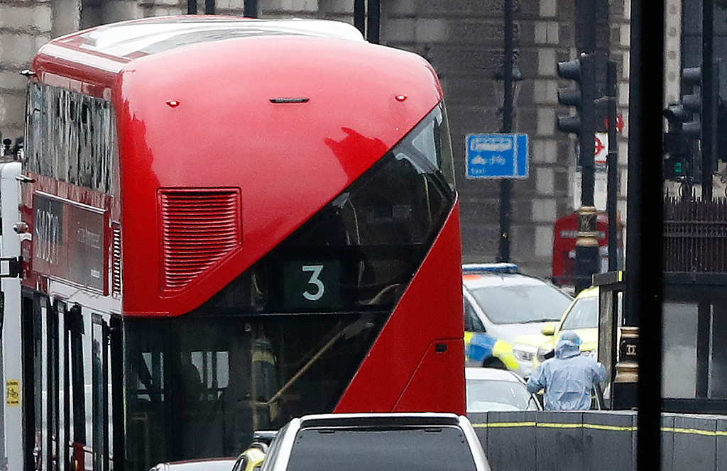 . A forensics officers works near the scene near a car that crashed into security barriers outside the Houses of Parliament to the right of a bus in London, Tuesday, Aug. 14, 2018. London police say that a car has crashed into barriers outside the Houses of Parliament and that there are a number of injured. (AP Photo/Alastair Grant)