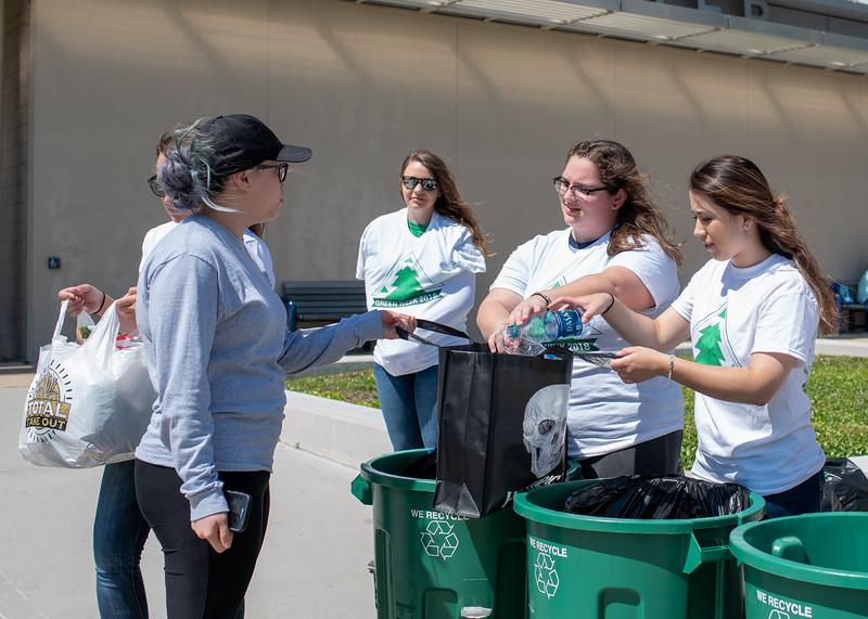 Islander student, Denise Garza turns in recyclable water bottles during Student Volunteer Connection's recycling event.