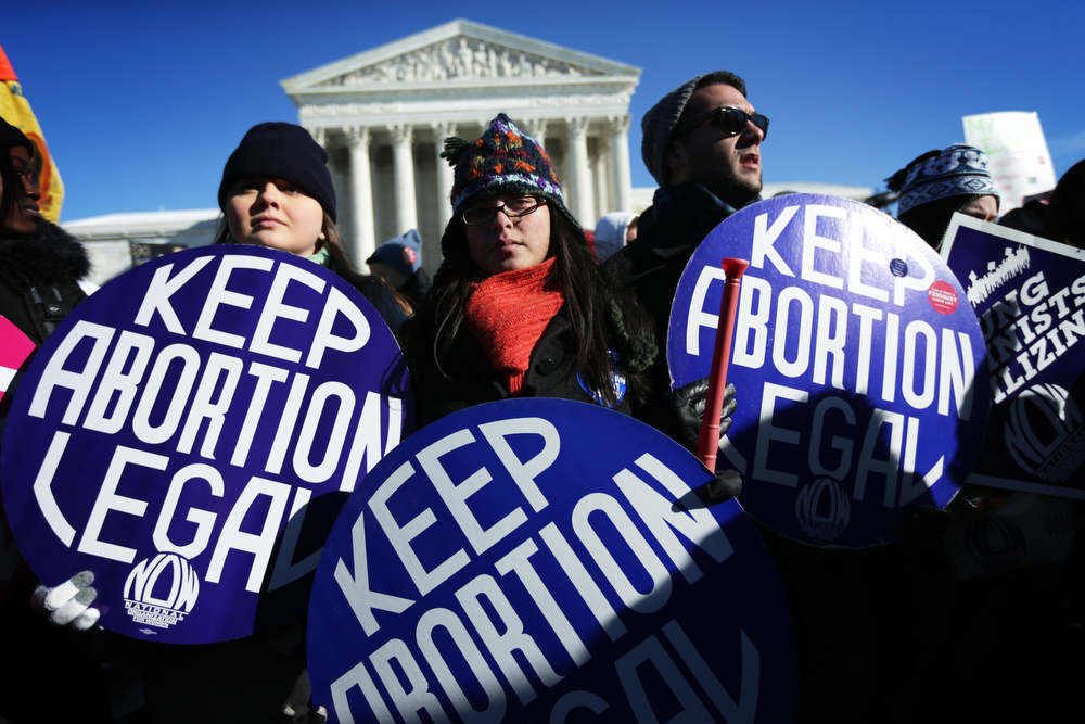 . Pro-choice activists hold signs as marchers of the annual March for Life arrive in front of the U.S. Supreme Court January 22, 2014 on Capitol Hill in Washington, DC. Pro-life activists from all around the country gathered in Washington for the event to protest the Roe v. Wade Supreme Court decision in 1973 that helped to legalize abortion in the United States.  (Photo by Alex Wong/Getty Images)