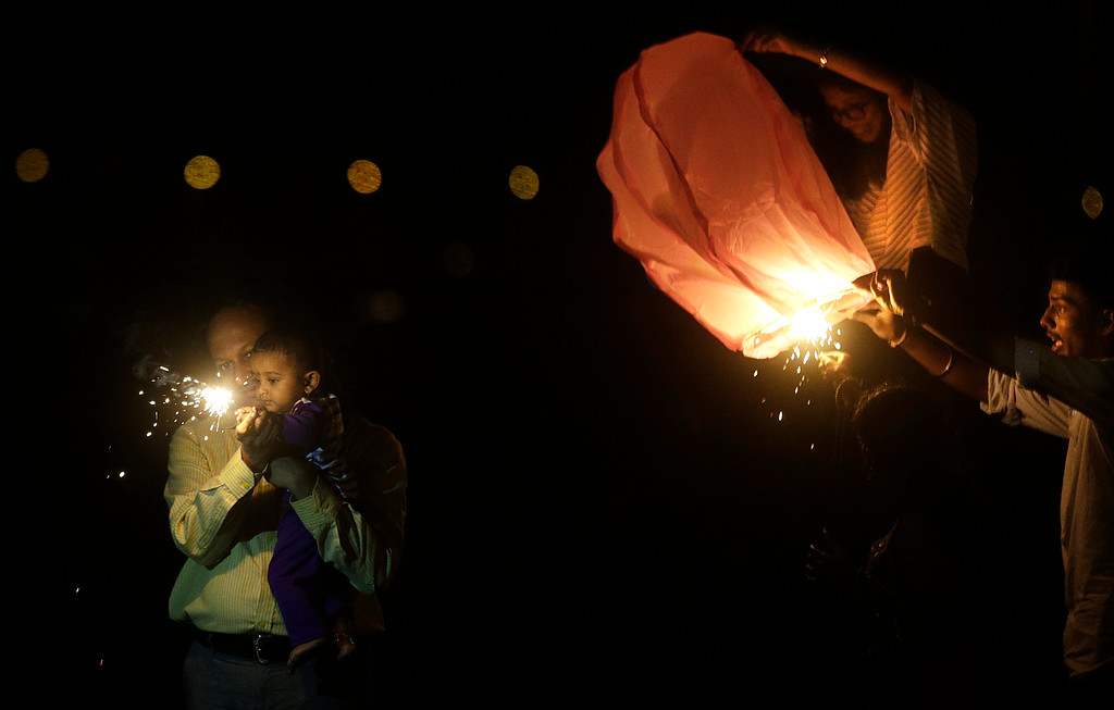 . An Indian child plays with a firecracker, as others light a sky lantern to celebrate Diwali, the Hindu festival of lights, in Mumbai India, Thursday, Oct. 19, 2017. (AP Photo/Rafiq Maqbool)
