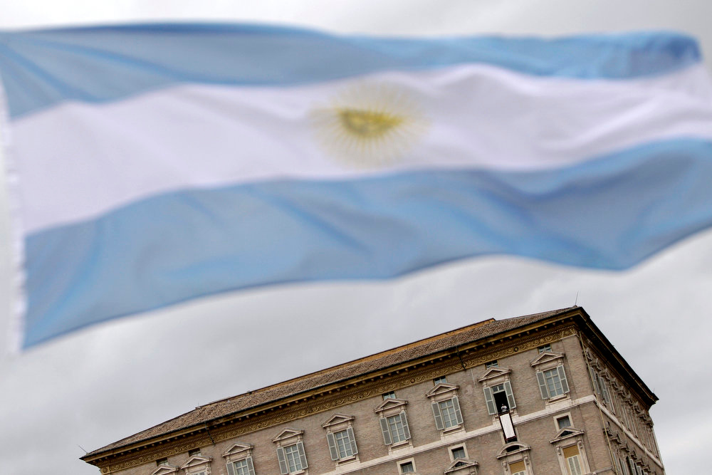 ". An argentine flag waves as Pope Francis, in background, recites his first Angelus prayer from his studio window overlooking St. Peter\'s square at the Vatican, Sunday, March 17, 2013. Breaking with tradition, Pope Francis delivered off-the-cuff remarks about God\'s power to forgive instead of reading from a written speech for the first Sunday window appearance of his papacy. He also spoke only in Italian, beginning with ""buon giorno\"" (Good day) and ending with \""buon pranzo\"" (Have a good lunch), instead of greeting the faithful in several languages as his last few predecessors had done. (AP Photo/Riccardo De Luca)"
