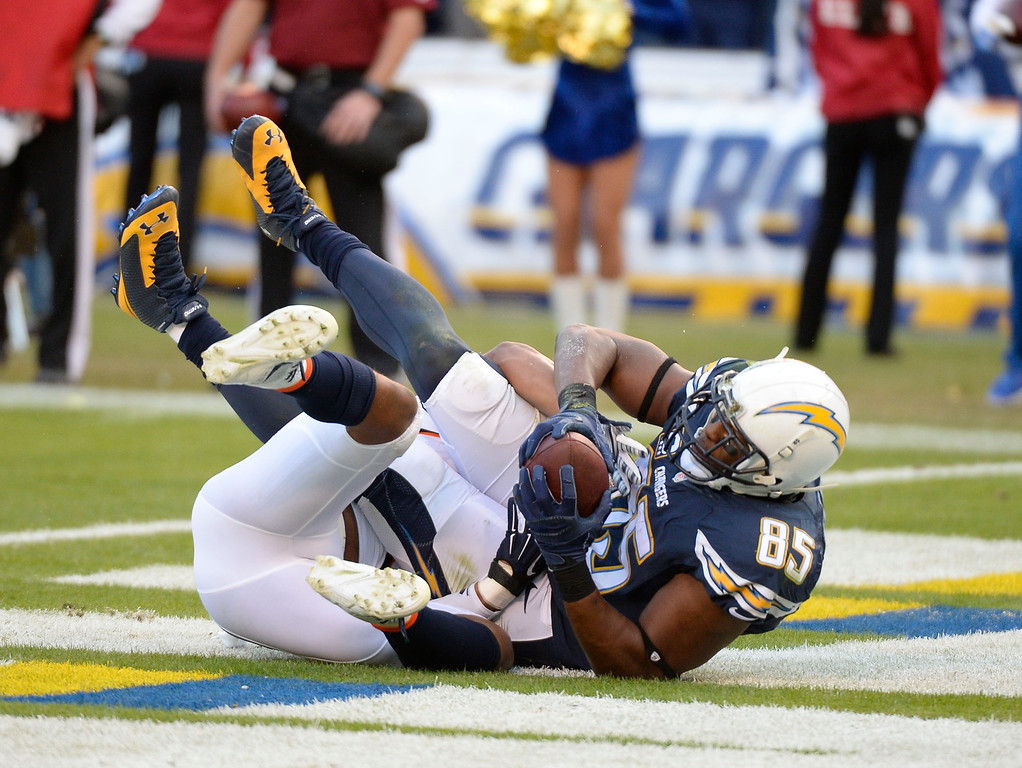 . SAN DIEGO, CA - DECEMBER 14: San Diego Chargers tight end Antonio Gates (85) lands on top of Denver Broncos strong safety T.J. Ward (43) after his touchdown catch during the third quarter December 14, 2014 at Qualcomm Stadium (Photo By John Leyba/The Denver Post)