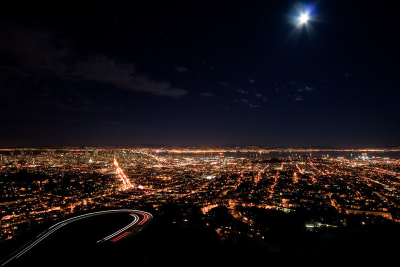 City lights of San Francisco, moon, and car trails from Twin Peaks