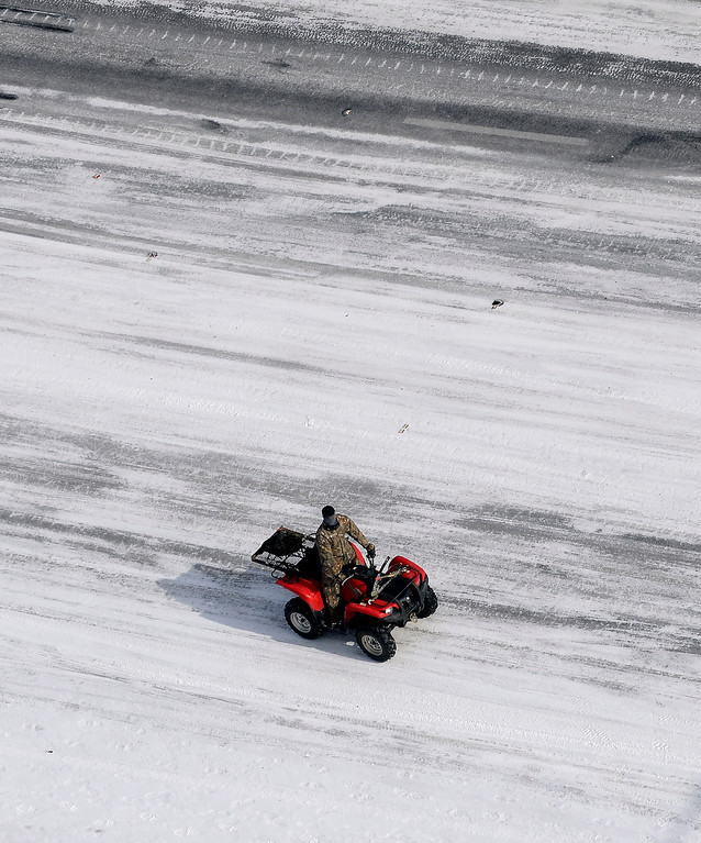 . In this aerial view, A good Samaritan on a four-wheeler patrols I-75 south at West Paces Ferry Rd. after a winter snow storm Wednesday, Jan. 29, 2014, in Atlanta.  Georgia Gov. Nathan Deal said early Wednesday that the National Guard was sending military Humvees onto Atlanta\'s snarled freeway system in an attempt to move stranded school buses and get food and water to people. Georgia State Patrol troopers headed to schools where children were hunkered down early Wednesday after spending the night there, and transportation crews continued to treat roads and bring gas to motorists, Deal said.  (AP Photo/David Tulis)