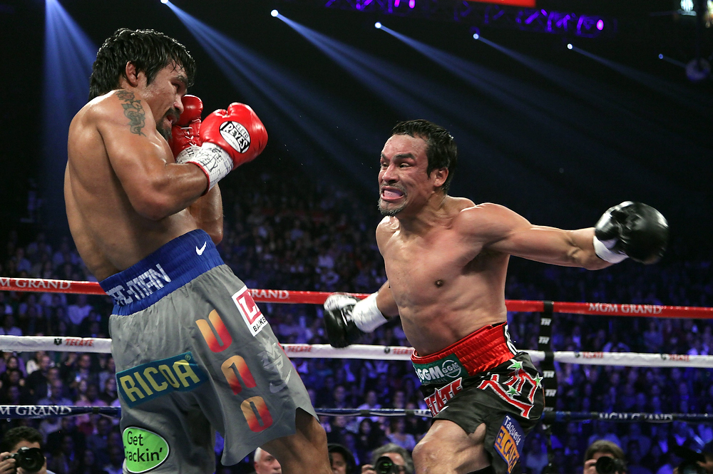 . Manny Pacquiao, left, and Juan Manuel Marquez battle during their welterweight fight on December 8, 2012, at the MGM Grand Garden in Las Vegas, Nevada.  Marquez knocked out Pacquiao in the 6th round.  JOHN GURZINSKI/AFP/Getty Images