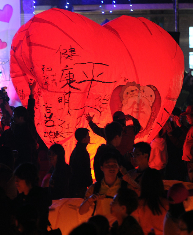 . Local residents release a heart-shaped sky lantern in Pingshi, the New Taipei City, on the fifth day of the lunar new year on February 14, 2013.  At least 600 couples celebrated their Valentine\'s day via releasing sky lenterns on the lunar new year of snake.  AFP PHOTO / Sam  YEH/AFP/Getty Images