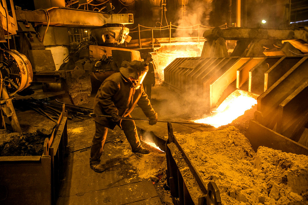 . An employee works in front of the blast furnace at the Zaporizhstal steel plant, owned and operated by Metinvest BV, at their site in Zaporizhzhya, Ukraine, on Monday, Oct. 14, 2013. Metinvest BV, Ukraine\'s largest steelmaker, last year acquired 49.9% in steelmaker Zaporizhstal a manufacturer of semi-finished steel products, including hot and cold-rolled plates and coils. Photographer: Vincent Mundy/Bloomberg