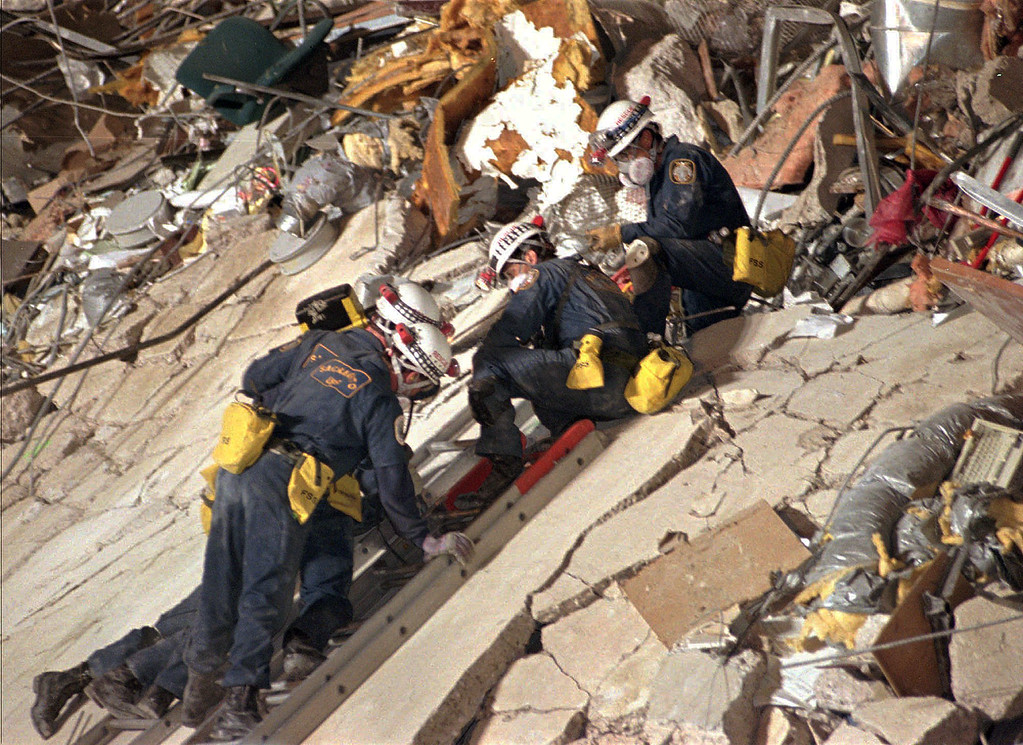 . FILE - In this April 20, 1995 file photo, rescue crews work together as they climb over areas of debris at the Alfred P. Murrah Federal Building in Oklahoma City, searching for victims of the deadly car bombing. The blast killed 168 people - including 19 children - injured hundreds more and caused hundreds of millions of dollars in damage to structures and vehicles in the downtown area.  (AP Photo/David J. Phillip,Pool)