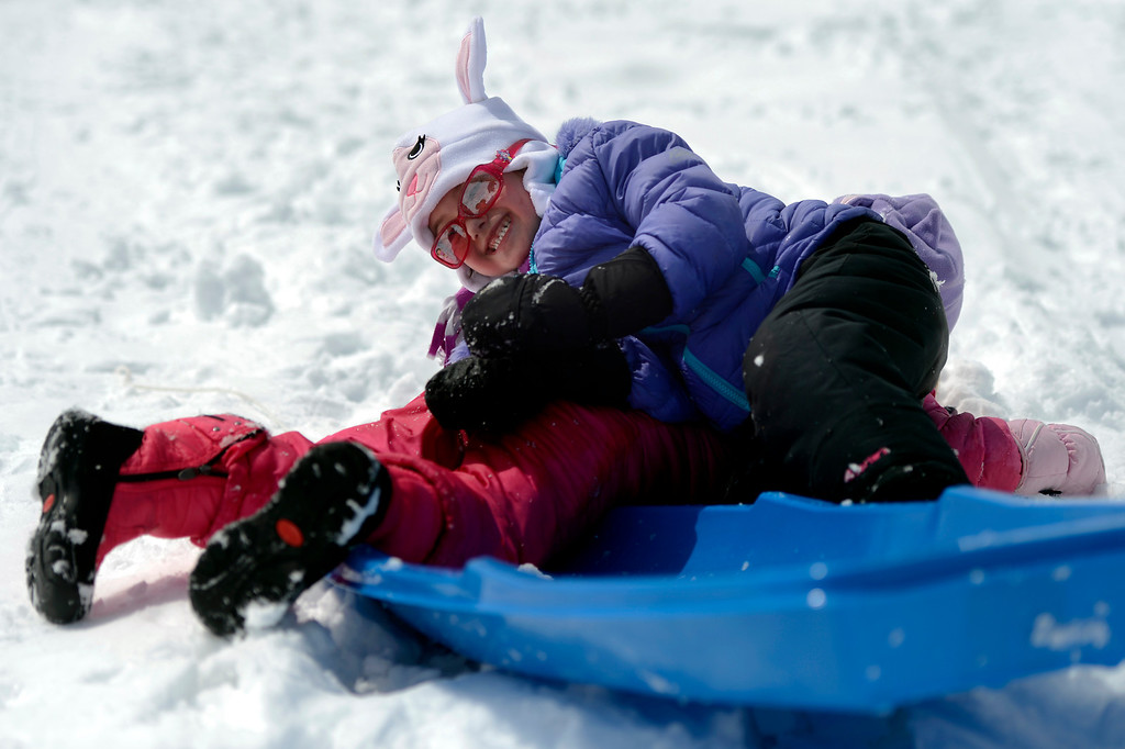. BOULDER, CO. - APRIL 23: 4 year old Erin Doyle is bowled over by her twin sister Megan n pink as they sled at Scott Carpenter Park April 23, 2013 Boulder, Colorado. (Photo By Joe Amon/The Denver Post)