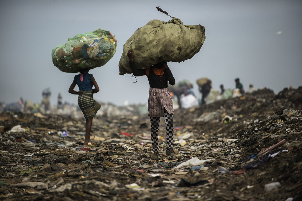 . Girls carry bags of plastic items and tins as rubbish pickers sift through garbage at the Maputo municipal garbage dumping site in Maputo on October 14, 2014. GIANLUIGI GUERCIA/AFP/Getty Images