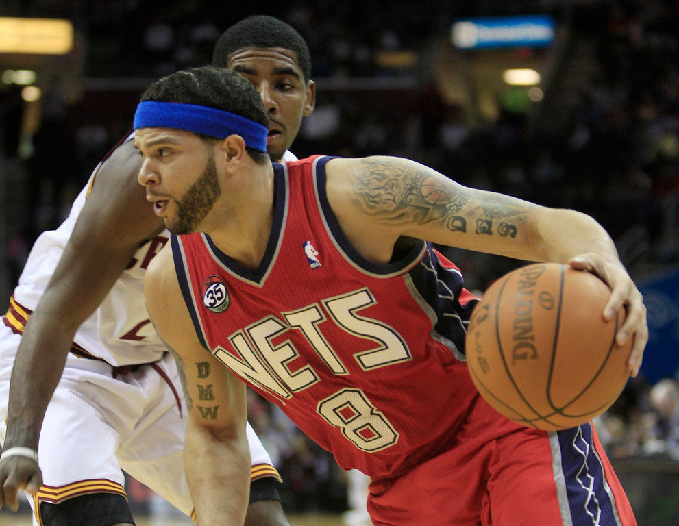 . New Jersey Nets point guard Deron Williams (8) drives around Cleveland Cavaliers\' Kyrie Irving (2) in the first quarter in an NBA basketball game on Friday, Jan. 27, 2012, in Cleveland. (AP Photo/Tony Dejak)