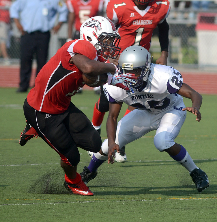 . Southfield-Lathrup running back #7 Adrian Church puts a move on Pontiac High School defender during their game at Southfield Lathrup High School, Thursday August 29, 2013. (Oakland Press Photo:Vaughn Gurganian)
