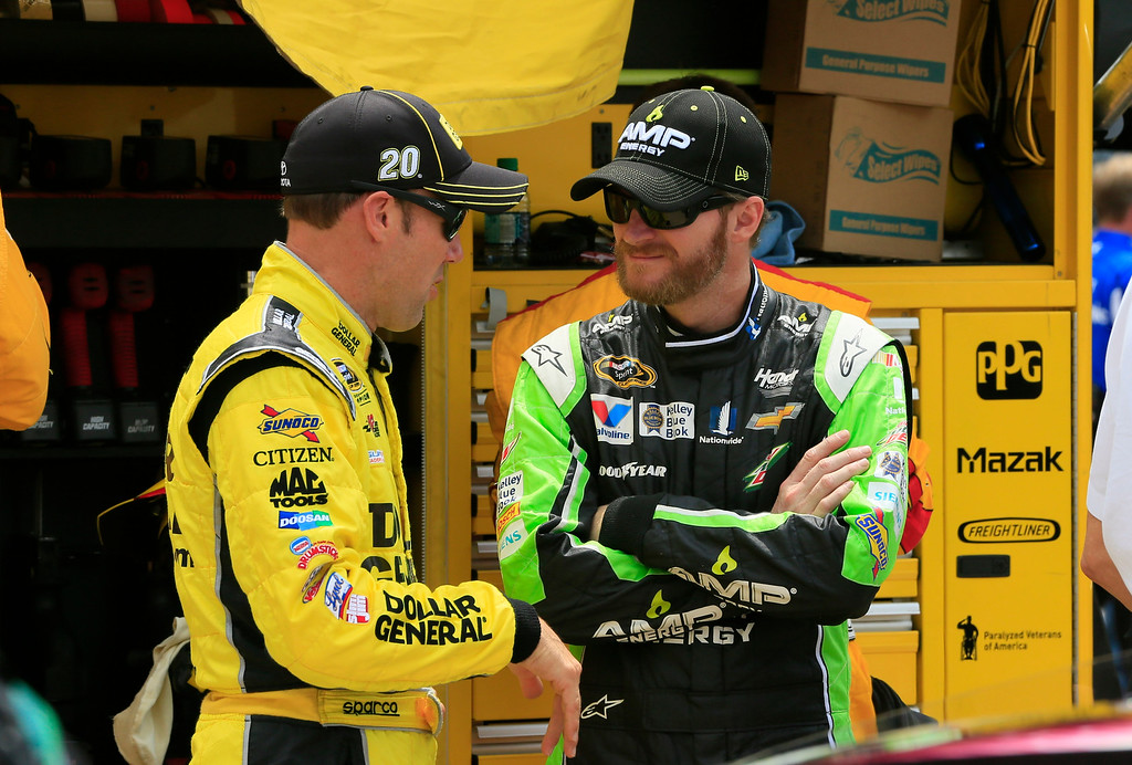 . Matt Kenseth, left, talks with Dale Earnhardt Jr. before the NASCAR Sprint Cup series auto race at Michigan International Speedway, Sunday, June 14, 2015, in Brooklyn, Mich. (AP Photo/Carlos Osorio)
