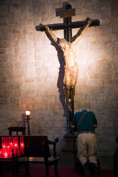 Un hombre reza arrodillado ante la figura de un crucificado, Santa María del Mar, Barcelona