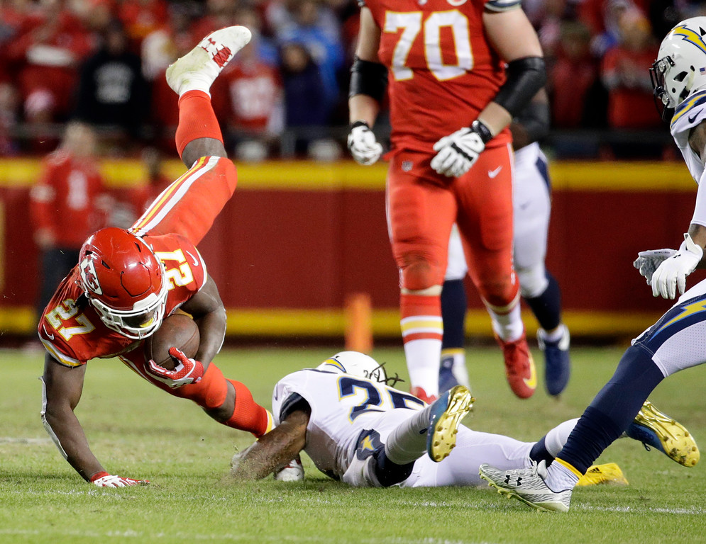 . Kansas City Chiefs running back Kareem Hunt (27) is tackled by Los Angeles Chargers safety Rayshawn Jenkins (25) during the second half of an NFL football game in Kansas City, Mo., Saturday, Dec. 16, 2017. (AP Photo/Charlie Riedel)