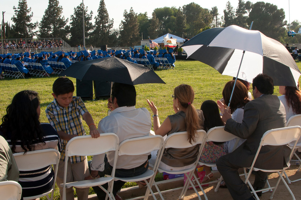 . Parents use umbrellas to shade themselves from the sun during the ceremony.  The Reseda High School graduation class held their commencement in the school football field on Friday,  June 07, 2013 in Reseda, CA.   Photo by Carlos Carpio