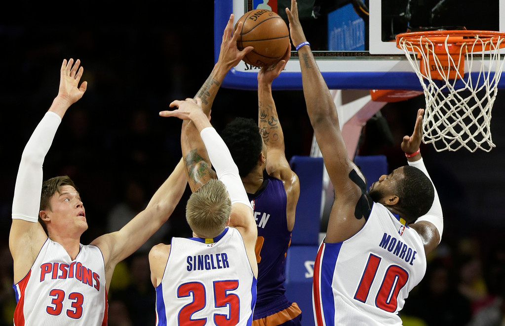. Phoenix Suns guard Gerald Green makes a basket while defended by Detroit Pistons forwards Jonas Jerebko (33), Kyle Singler (25) and Greg Monroe (10) during the first half of an NBA basketball game in Auburn Hills, Mich., Wednesday, Nov. 19, 2014. (AP Photo/Carlos Osorio)