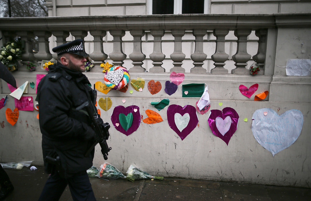. An armed policeman walks past a wall at the French Embassy covered on sympathy messages  on January 8, 2015 in London, United Kingdom. France is on maximum security threat level after twelve people were killed, including two police officers, at the offices of the satirical magazine Charlie Hebdo in Paris. French Police have made seven arrests in connection with the attack in which they have named two main suspects, brothers Cherif and Said Kouachi. A further blow to the country came this morning when a gunman killed a policewoman in the southern suburb of Montrouge.  (Photo by Peter Macdiarmid/Getty Images)