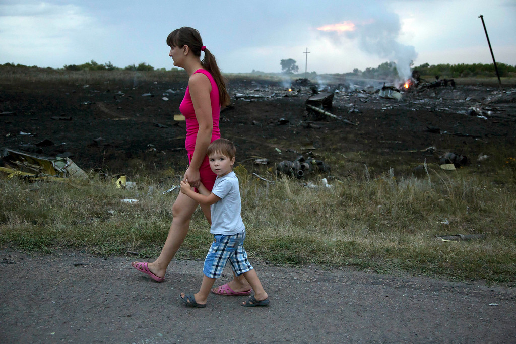 . A woman with a child walks past the crash site of a passenger plane near the village of Grabovo, Ukraine, Thursday, July 17, 2014. Ukraine said a passenger plane carrying 295 people was shot down Thursday as it flew over the country, and both the government and the pro-Russia separatists fighting in the region denied any responsibility for downing the plane. (AP Photo/Dmitry Lovetsky)