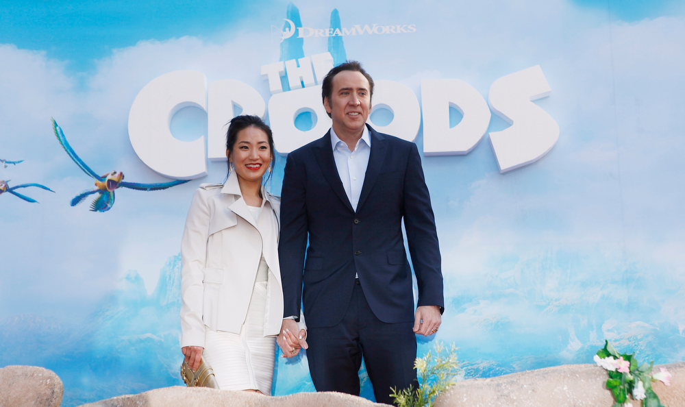 """. Actor Nicolas Cage and wife Alice Kim arrive for the premiere of the film \""""The Croods\"""" in New York, March 10, 2013. REUTERS/Carlo Allegri"""