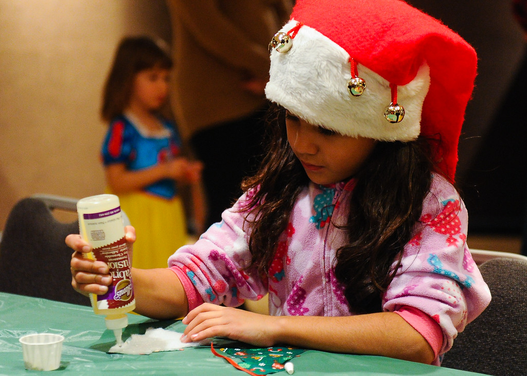 . Franchesca (cq) Mercado, 8, makes holiday crafts during the annual Santa Pajama Party at the San Bernardino County Museum in Redlands on Friday, Dec. 6, 2013. (Photo by Rachel Luna / Redlands Daily Facts)