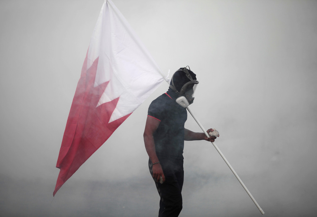 . A Bahraini anti-government protester, masked against the tear gas, carries a national flag and stones during clashes with riot police in the village of Shakhura, Bahrain, on Wednesday, Aug. 14, 2013. Bahraini protesters clashed with riot police in neighborhoods around the capital Wednesday and stores shut their doors amid opposition calls for a general strike, but a tight security clampdown appears to have stopped large-scale demonstrations in the city. (AP Photo/Hasan Jamali)