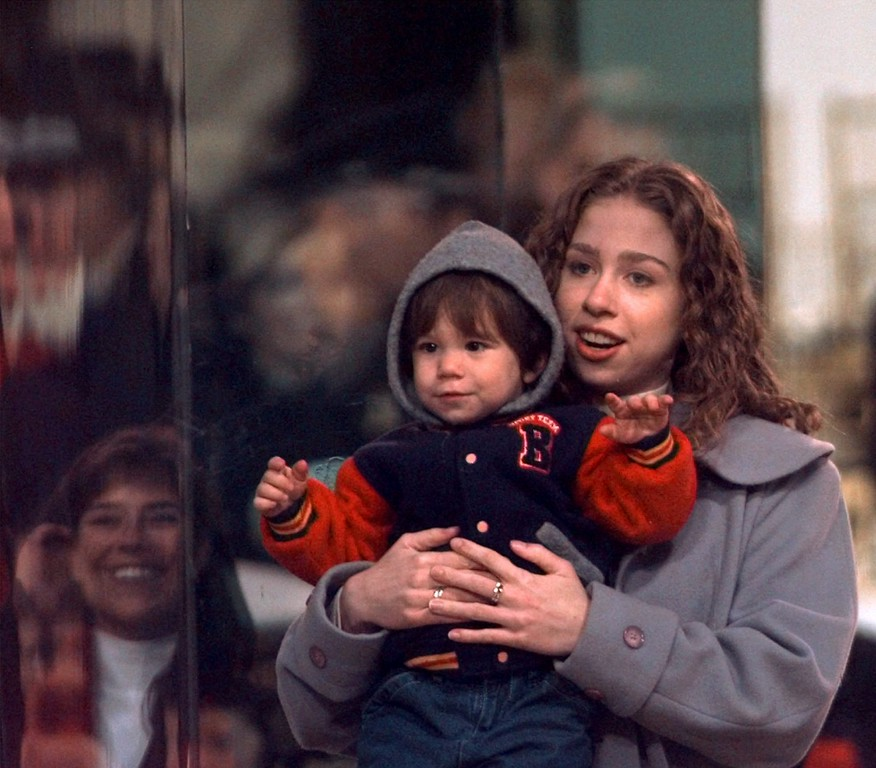 . Chelsea Clinton holds Roger Clinton\'s son Tyler as they watch the inaugural parade from the reviewing stand Monday, Jan. 20, 1997, in Washington. (AP Photo/Rick Bowmer)