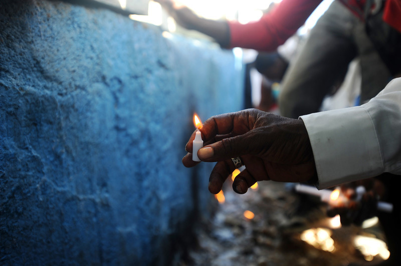 . man puts a candle at the foot of a cross during the pilgrimage at Morne Calvaire on Good Friday in Port-au-Prince on April 18, 2014.  (HECTOR RETAMAL/AFP/Getty Images)
