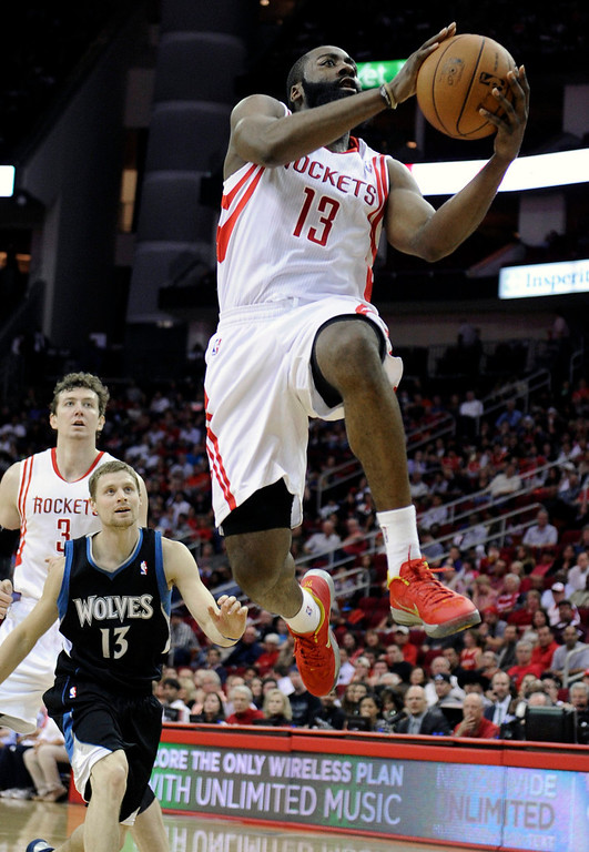 . Houston Rockets\' James Harden goes to the basket as Minnesota Timberwolves\' Luke Ridnour, center, looks on in the second half Friday, March 15, 2013, in Houston. The Rockets won 108-100. (AP Photo/Pat Sullivan)