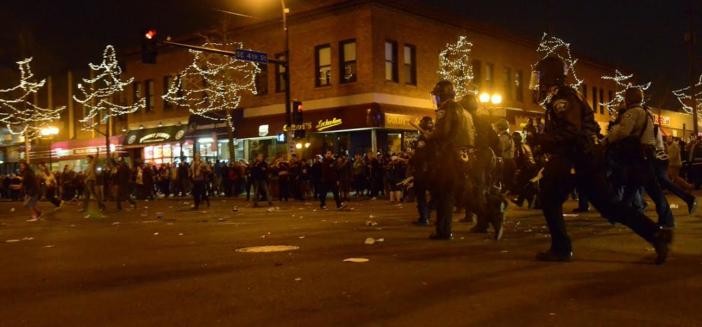 . Police lunge after crowds starting to disburse at Fourth Street and Fourteenth Avenue S.E. on Saturday night. (Pioneer Press: C.J. Sinner)