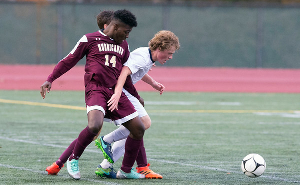 10/29/19 Wesley Bunnell | StaffrrNew Britain soccer was defeated 2-0 by Newington during a drizzle at Veterans Stadium on Tuesday afternoon. New Britain's Jerry Chungong (14) and Newington's Ryan Saindon (11).