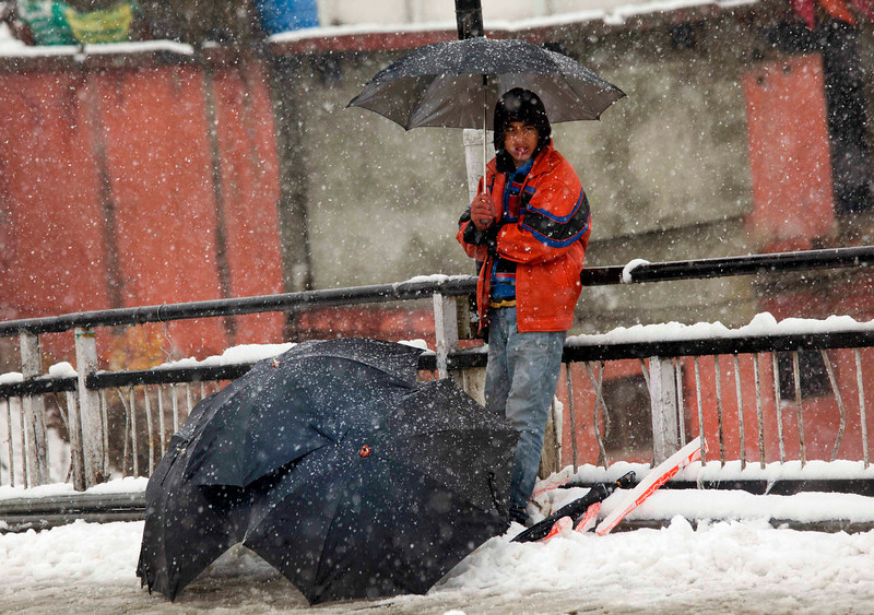 . A Kashmiri Muslim boy sells umbrellas as it snows in Srinagar, India, Friday, Jan. 18, 2013. Traffic on the 300 kilometers (186 miles)-long Jammu-Srinagar national highway was suspended due to heavy snowfall, according to news reports. (AP Photo/Dar Yasin)