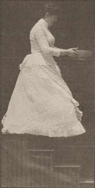 Woman descending stairs holding a basin in her hands