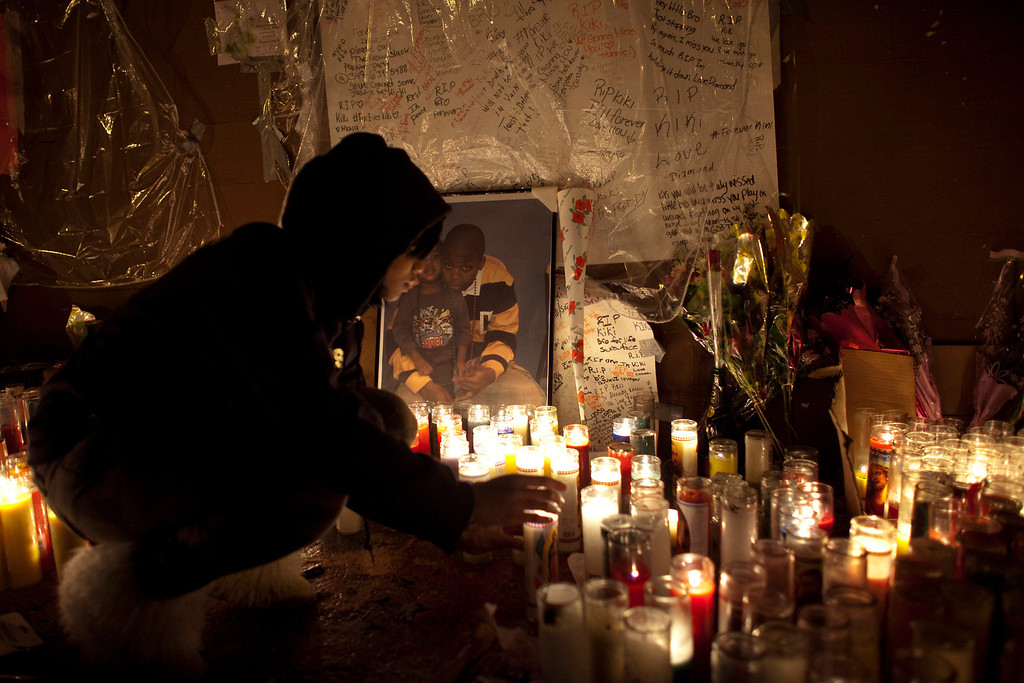 ". A mourner lights candles at a memorial for 16-year-old Kimani ""Kiki\"" Gray who was killed in a shooting involving the New York Police Department, in the Brooklyn borough of New York March 13, 2013. REUTERS/Eduardo Munoz"