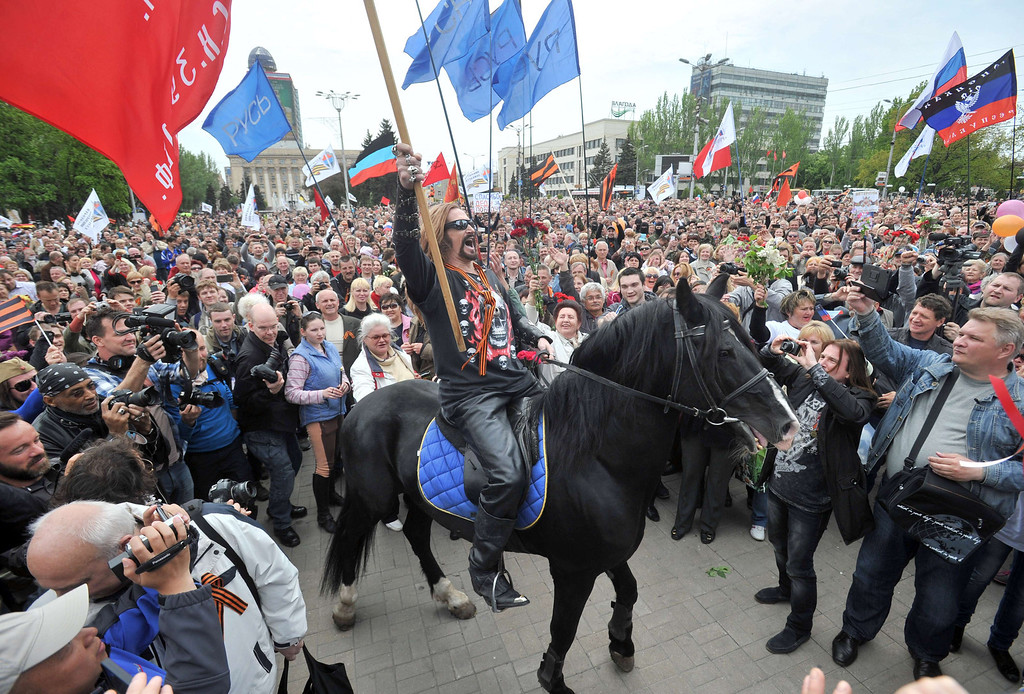 . A pro-Russia activist waves a red flag as he rides a horse during a rally marking Victory Day in the eastern Ukrainian city of Donetsk on May 9, 2014. Ukraine\'s government protested Russian President Vladimir Putin\'s visit to annexed Crimea, where he inspected Russian naval forces in a commemoration of the Soviet victory in World War II. AFP PHOTO/ GENYA  SAVILOV/AFP/Getty Images