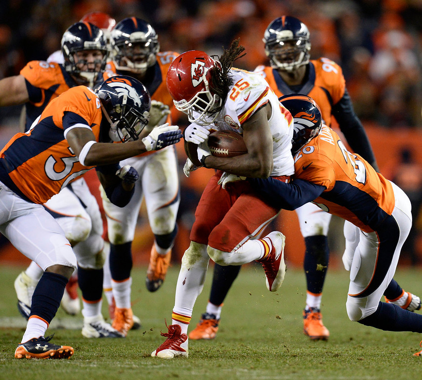 . Kansas City Chiefs running back Jamaal Charles (25) is tackled by Denver Broncos strong safety Mike Adams (20) in the third quarter. The Denver Broncos take on the Kansas City Chiefs at Sports Authority Field at Mile High in Denver on November 17, 2013. (Photo by John Leyba/The Denver Post)